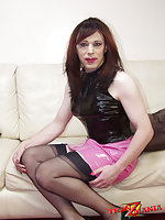Mature TS in latex outfit on sofa